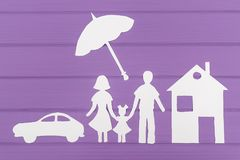 The silhouettes cut out of paper of man and woman with one girl under the umbrella, house and car near royalty free stock photos