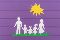 The silhouettes cut out of paper of man and woman with two girls and boy on the grass under the sun Stock Photography
