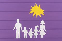The silhouettes cut out of paper of man and woman with two girls and boy under the sun Stock Photos