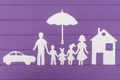 The silhouettes cut out of paper of man and woman with two girls and boy under the umbrella, house and car near Royalty Free Stock Image