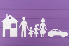 The silhouettes cut out of paper of man and woman with two girls, house and car near Royalty Free Stock Photos