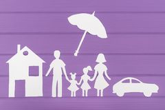The silhouettes cut out of paper of man and woman with two girls under the umbrella, house and car near Royalty Free Stock Photography