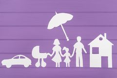 The silhouettes cut out of paper of man and woman with two girls under the umbrella, house and car near Stock Photos