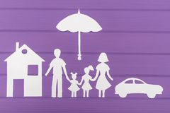 The silhouettes cut out of paper of man and woman with two girls under the umbrella, house and car near Royalty Free Stock Photos