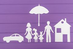 The silhouettes cut out of paper of man and woman with two girls under the umbrella, house and car near Stock Photo