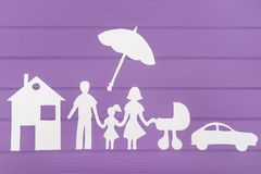 The silhouettes cut out of paper of man and woman with two girls under the umbrella, house and car near Royalty Free Stock Images