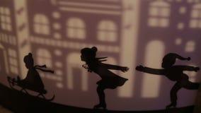 Silhouettes décoratives des enfants patinant sur un traîneau et une projection de ville banque de vidéos