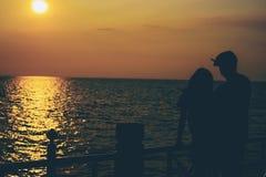 Silhouettes d'étreindre des couples contre la mer au coucher du soleil Photo stock