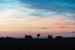 Silhouettes d'arbre par un ciel coloré Photographie stock