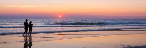 Silhouettes d'un couple appréciant le coucher du soleil sur l'Océan Atlantique, France de Lacanau Image stock