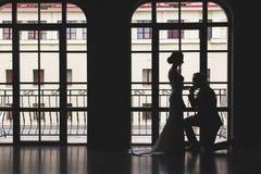 Silhouettes d'un homme dans un costume et des femmes dans une robe et avec un bouquet des fleurs L'homme s'est mis ? genoux vers  photo stock
