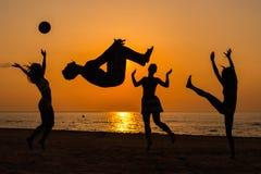Silhouettes d'un peuple ayant l'amusement sur une plage Image stock