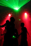 Silhouettes of dacing people. Green laser/red scanner light Stock Image