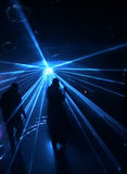 Silhouettes of dancing people. In front of blue laser lights Royalty Free Stock Image