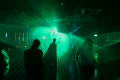 Silhouettes of dancing people. Between laser light in a disco stock image