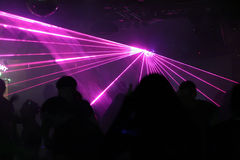 Silhouettes of dancing people. Between purple laser light royalty free stock photos