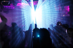Silhouettes of dancing people. Between blue laser light stock image