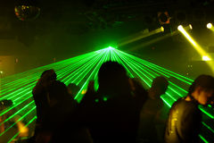 Silhouettes of dancing people. Between green laser in a disco Stock Image