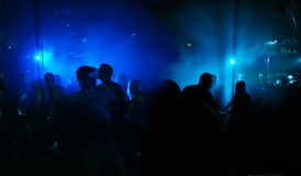 Silhouettes of dancing people. Produced by blue scanner-lights in a discotheque royalty free stock photo