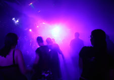 Silhouettes of dancing people. Highlighted by blue/purple lights stock image