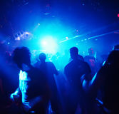 Silhouettes of dancing people. Highlighted by blue lights Royalty Free Stock Photography