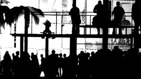 Silhouettes of dancing people on the balcony above the crowd. Silhouettes of dancing people on a balcony over a crowd on a white background stock footage