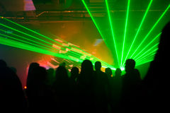 Silhouettes of dancing people in green laser light. S at disco club Royalty Free Stock Photos