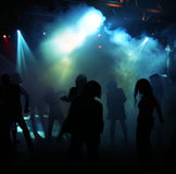 Silhouettes of a dancing teenagers. Dancing people in a disco between fog Stock Photography