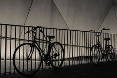 Silhouettes de bicyclette contre la balustrade la nuit Photo stock