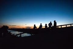 Silhouettes de cinq personnes sur le pont au crépuscule Photographie stock libre de droits