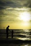 Silhouettes de coucher du soleil de père et de fille par la mer Images stock
