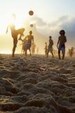 Silhouettes de coucher du soleil jouant le football Brésil de plage d'Altinho Futebol Images libres de droits