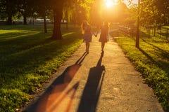 Silhouettes de deux amies marchant tenant des mains en parc Image stock