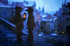 Silhouettes de deux enfants, tenant sur des escaliers, tenant une lanterne Photographie stock libre de droits