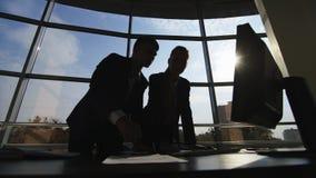 Silhouettes de deux hommes d'affaires travaillant avec un ordinateur sur un fond de fenêtre dans un grand bureau lumineux banque de vidéos