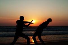 Silhouettes de deux jeunes hommes jouant sur la plage pendant le coucher du soleil Image stock