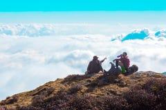Silhouettes de deux voyageurs s'asseyant sur la haute falaise au-dessus du ciel Photographie stock