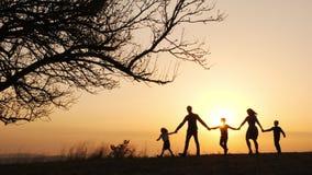 Silhouettes de famille heureuse marchant ensemble dans le pré pendant le coucher du soleil banque de vidéos