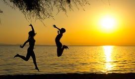 Silhouettes de fille et de garçon sautant sur la plage au coucher du soleil Images stock