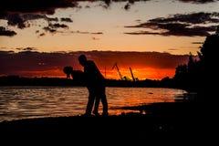 Silhouettes de jeunes couples affectueux sur le ciel et la mer lumineux de coucher du soleil Photo stock