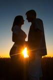 Silhouettes de jeunes couples au coucher du soleil Photo stock