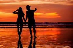Silhouettes de jeunes couples dans l'amour staing sur Image stock