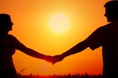 Silhouettes de jeunes couples de sourire heureux dans le domaine de blé d'été Photo stock