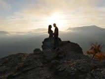 Silhouettes de jeunes couples se tenant sur une montagne et regardant entre eux sur le beau fond de coucher du soleil Amour de ty Photographie stock libre de droits