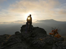 Silhouettes de jeunes couples se tenant sur une montagne et regardant entre eux sur le beau fond de coucher du soleil Amour de ty Photo stock