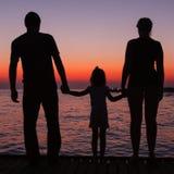 Silhouettes de l'homme, de femme et d'enfant sur le fond du soleil Image stock