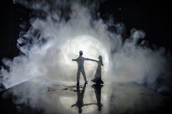 Silhouettes de la danse de couples de jouet sous la lune la nuit Figures de l'homme et de femme dans la danse d'amour au clair de Image stock