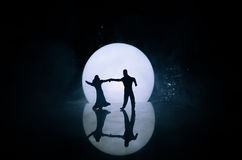 Silhouettes de la danse de couples de jouet sous la lune la nuit Figures de l'homme et de femme dans la danse d'amour au clair de Image libre de droits