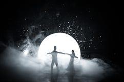 Silhouettes de la danse de couples de jouet sous la lune la nuit Figures de l'homme et de femme dans la danse d'amour au clair de Images stock