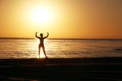 Silhouettes de la fille avec les mains augmentées sur un fond d'un lever de soleil images libres de droits